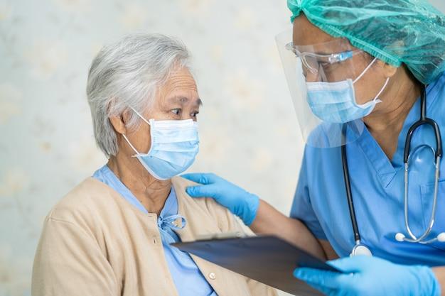 Доктор проверяет азиатскую пожилую женщину-пациента в маске для защиты от коронавируса covid-19.