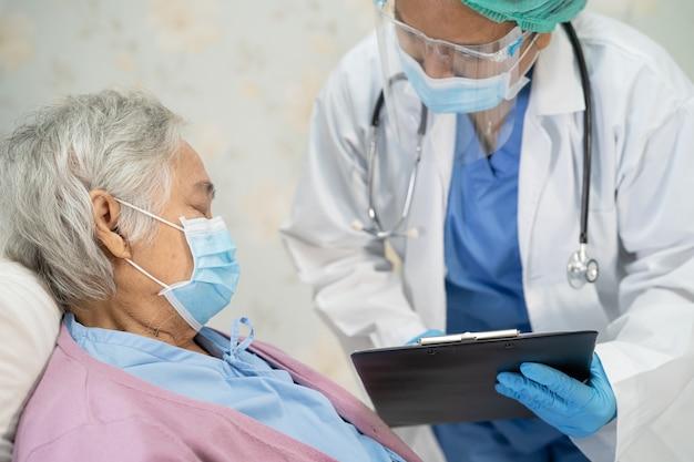 Covid19コロナウイルスを保護するためにフェイスマスクを着用しているアジアの年配の女性患者をチェックする医師