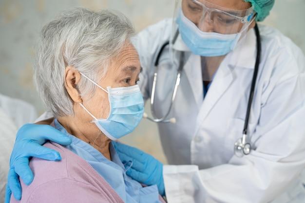 感染コロナウイルスを保護するためにフェイスマスクを身に着けているアジアの年配の女性患者をチェックする医師