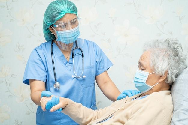 Covid-19コロナウイルスを保護するために病院でフェイスマスクを着用しているアジアの年配の女性患者をチェックする医師。