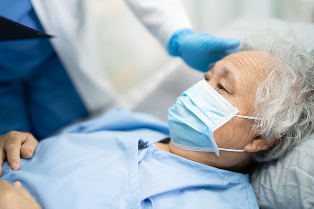 感染を防ぐために病院でフェイスマスクを着用しているアジアの年配の女性患者をチェックする医師covid19コロナウイルス