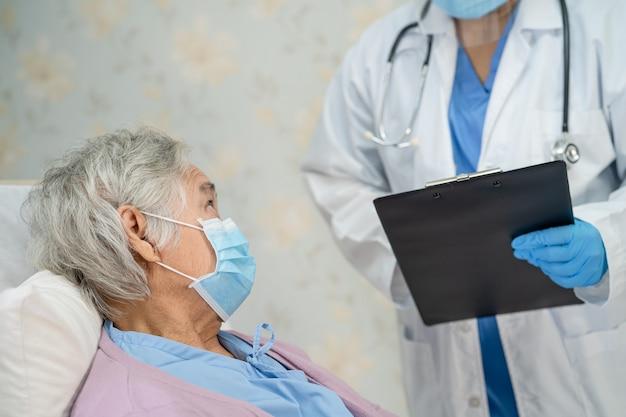 保護のために病院でフェイスマスクを着用しているアジアの年配の女性患者をチェックする医師コロナウイルス