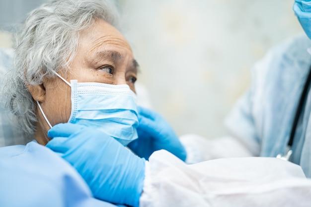 フェイスマスクを身に着けているアジアの年配の女性患者をチェックする医師