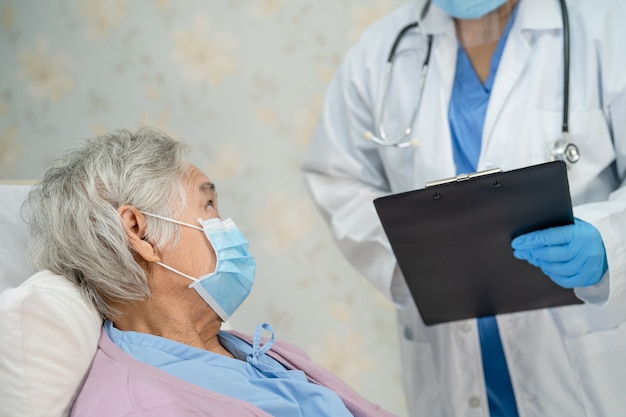 Doctor checking asian senior woman patient wearing a face mask in hospital for protectcoronavirus