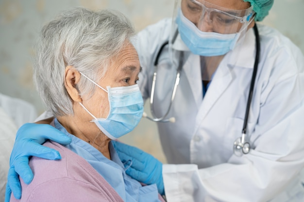 Doctor checking asian senior woman patient wearing a face mask for protect infection coronavirus