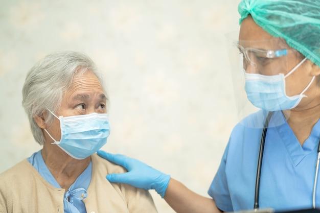 コロナウイルスを保護するためにマスクを身に着けているアジアの年配の女性患者をチェックする医師
