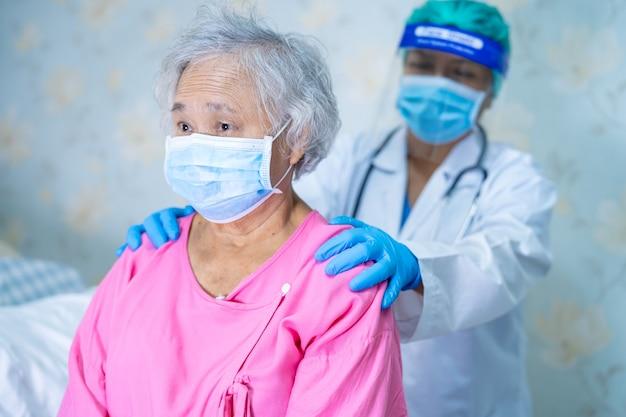 コロナウイルスcovid-19ウイルスを保護するためにフェイスマスクを着用しているアジアの女性患者をチェックする医師。
