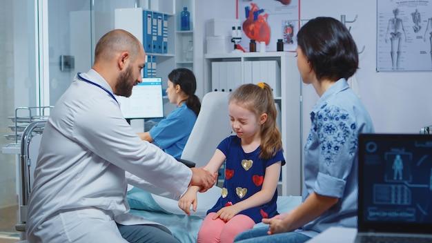 의사가 아이가 다친 팔을 확인하고 어머니와 이야기하고 있습니다. 의료 서비스를 제공하는 의료 전문가 의사 병원 캐비닛에서 방사선 치료 검사