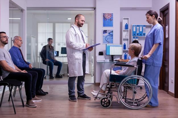 Medico che controlla la diagnosi di una donna anziana disabile paralizzata in sedia a rotelle seduta nella sala di ricevimento...