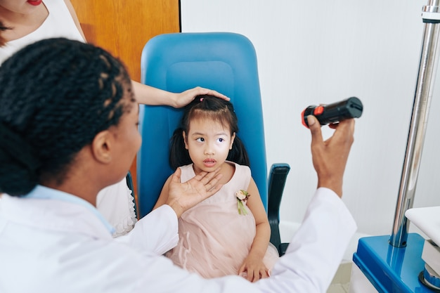 Doctor checking eyes of little girl with flashlight in medical room at the hospital