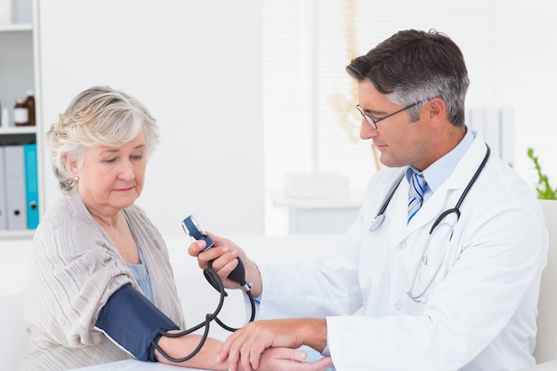 Doctor checking female patients blood pressure
