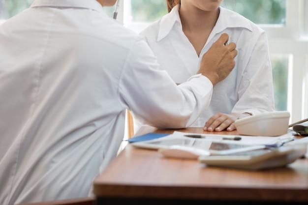 의사가 청진기로 심장 몸 환자를 검사하는 아시아 여성은 병원 책상 위에 클립보드를 놓고 아프다. 의료 의학 개념입니다.