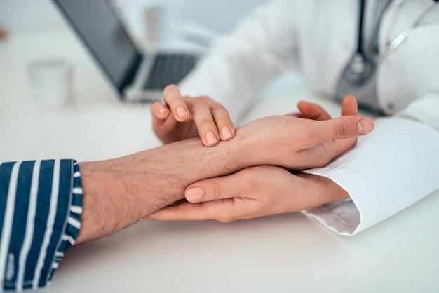 Доктор проверяя частоту сердечных сокращений пациента, конец-вверх.