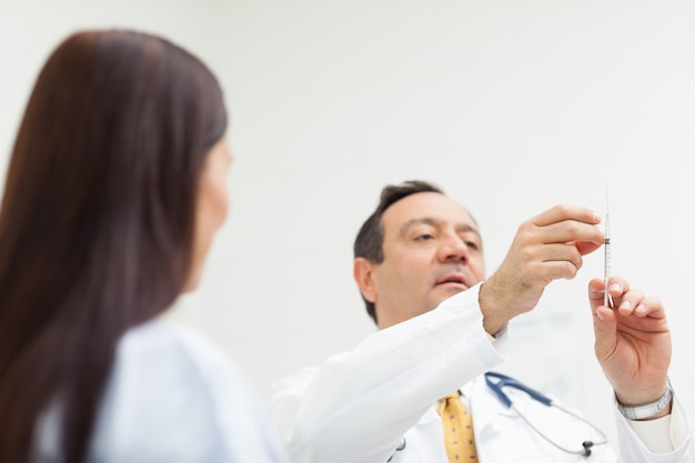 Doctor checking an injection for a patient