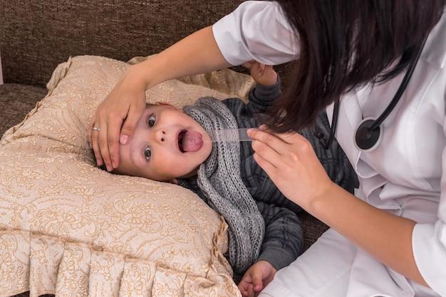 医者は小さな男の子の喉と頭の温度をチェックします