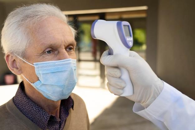 예방 접종 센터 외부 남성 환자의 온도를 확인하는 의사