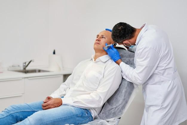 이경으로 남자의 귀를 검사하는 의사