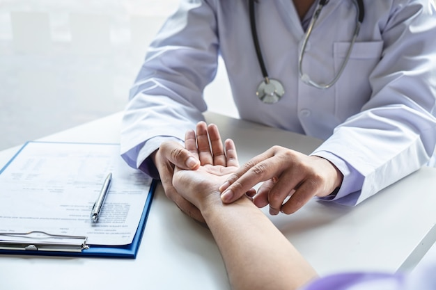 Doctor checking measuring pressure on patients hand pulse by hands