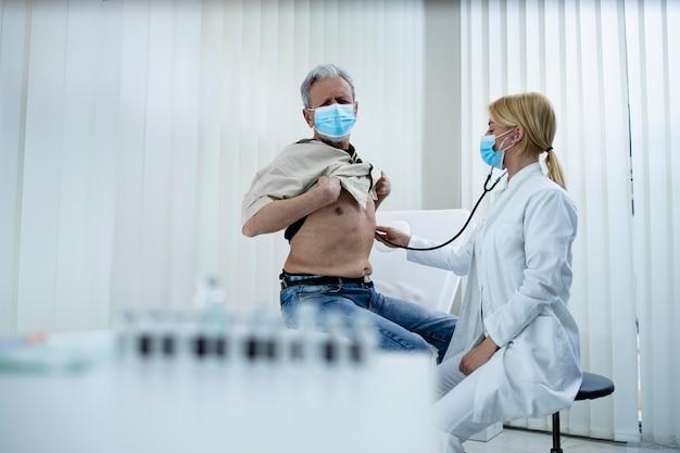 코로나 바이러스 전염병 동안 병원 사무실에서 청진기로 노인 호흡기 시스템과 폐를 검사하는 의사.