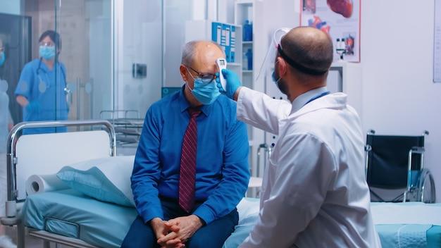 老人の体温を赤外線温度計でチェックする医師。相談のために保護具でマスクと医療従事者を身に着けている引退した年配の男性。現代の私立クリニック