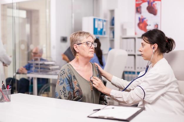 Доктор проверяет сердцебиение старухи с помощью стетоскопа в офисе больницы. инвалид старший мужчина в инвалидной коляске разговаривает с медиком в коридоре клиники.