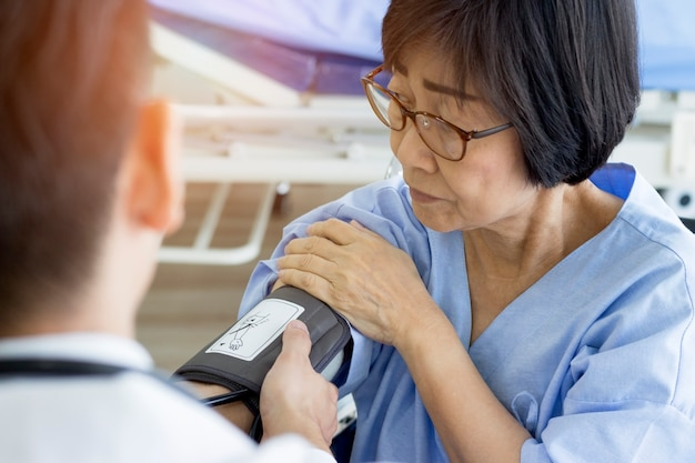Doctor checking old woman patient arterial blood pressure.