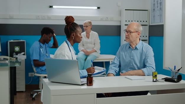 치료 시설의 의료 캐비닛에서 노인 환자의 건강을 확인하는 의사. 의무병은 책상에 앉아 있는 동안 검진 약속을 위해 노인에게 상담합니다. 클리닉에서 말하는 사람들