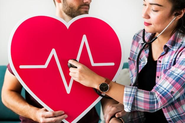 医者の聴診器で患者の心拍をチェック