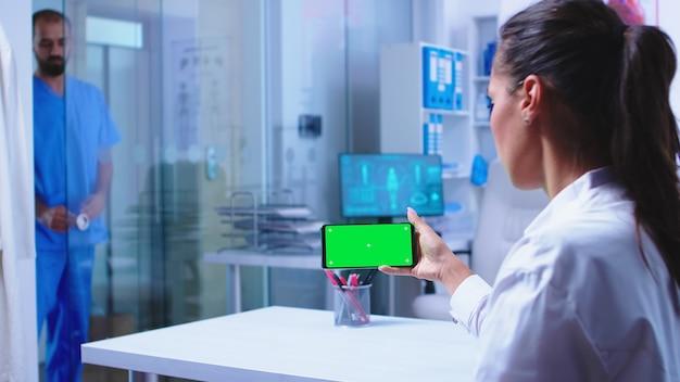 의사는 병원 캐비닛에 녹색 화면이 있는 스마트폰으로 환자 결과를 확인합니다. 파란색 의료 제복을 입은 간호사가 유리문을 닫습니다. mo와 함께 스마트폰을 사용하는 병원 캐비닛의 의료 전문가
