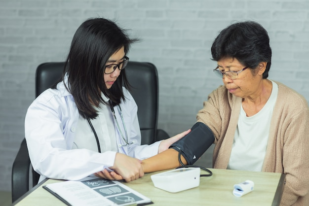 Doctor checking pressure old woman on gray