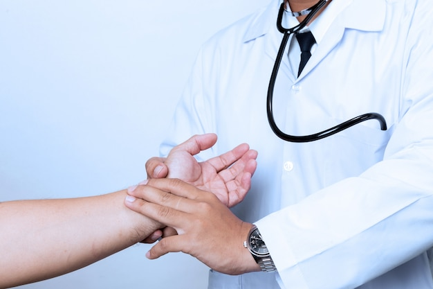 Doctor checking pulse by hand