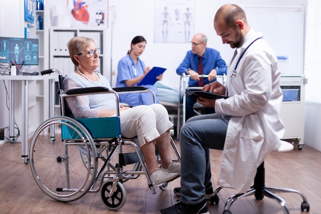건강 검진 중 휠체어를 탄 장애인 노인 여성의 회복 치료를 확인하는 의사