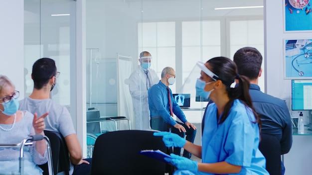 Врач проверяет легкие пожилого человека в смотровой в больнице, в маске от коронавируса. медсестра делает заметки во время обсуждения с женщиной-инвалидом в зоне ожидания.