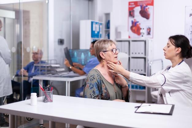 医師は年配の女性の喉の痛みをチェックし、セラピストは病室で年配の女性患者の首に触れている甲状腺の喉をチェックします。ヘルスケアスペシャリスト、メディケア、治療、医師の診察。