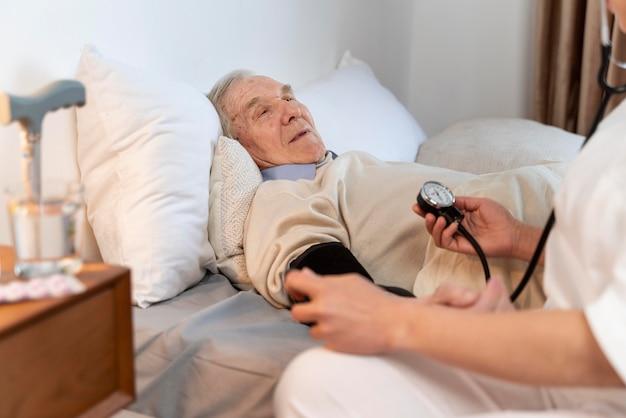 남성 환자의 혈압을 검사하는 의사