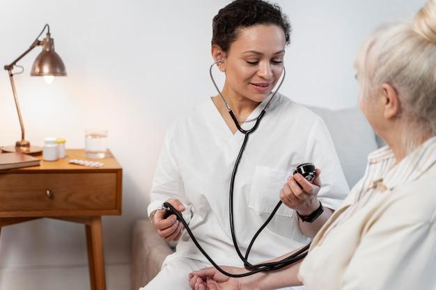 그녀의 환자의 혈압을 검사하는 의사