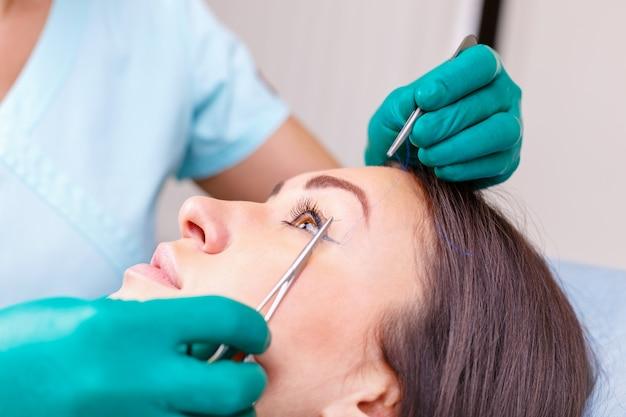 Врач проверяет женское лицо, веко перед пластической операцией, блефаропластикой.