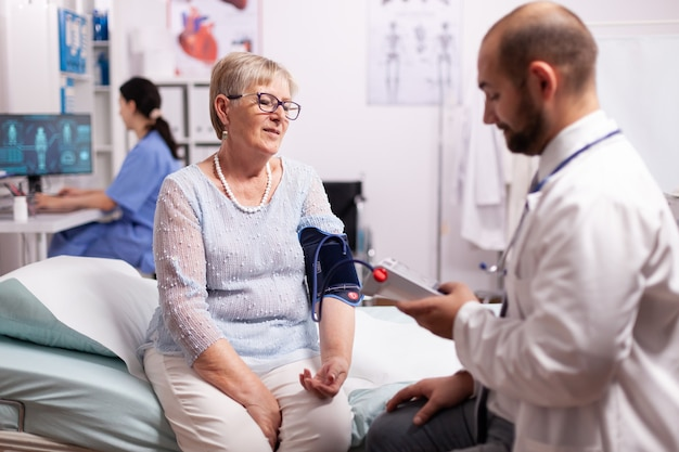 Doctor checking woman tension using portable arm digital preassure to check blood flow