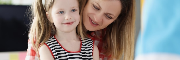 Doctor checks blood sugar level of little girl using digital glucometer at hospital