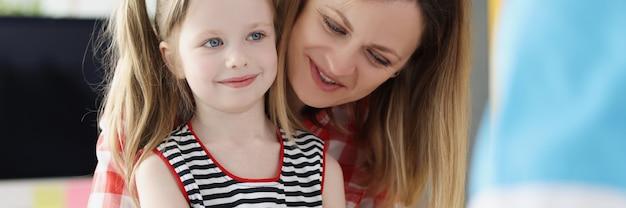 Врач проверяет уровень сахара в крови маленькой девочки с помощью цифрового глюкометра в больнице