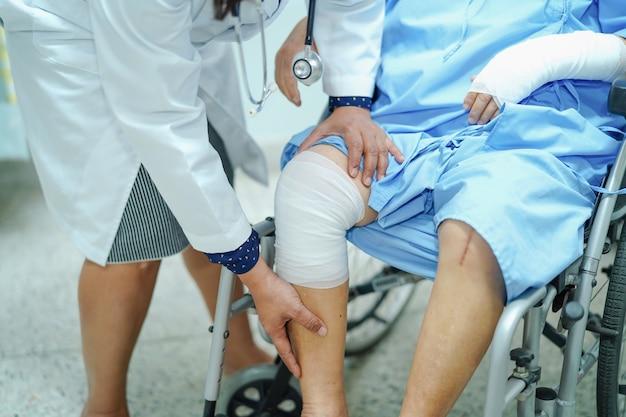 의사는 휠체어에 붕대로 무릎을 확인