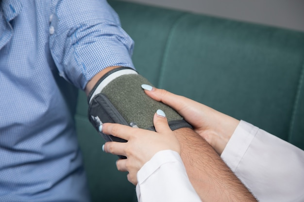 A doctor checks a man's blood pressure with an electronic device on the sofa