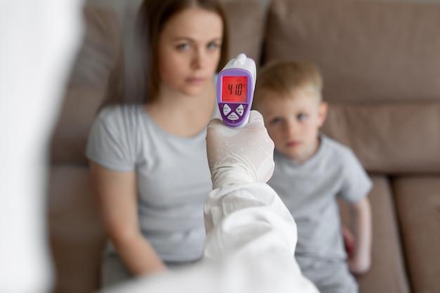 의사는 집에서 이마에 적외선 온도계 총을 사용하여 소녀와 아들의 체온을 확인합니다. 코로나 바이러스, 코 비드 -19, 고열 및 기침