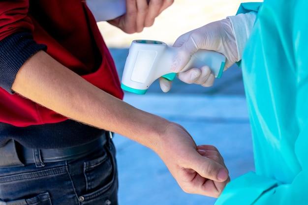 의사는 적외선 비접촉식 온도계로 소년 체온을 확인합니다.