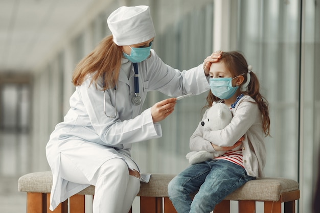 Doctor and a child in protective masks are in hospital