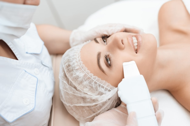 Doctor cleanses woman's skin with a special medical device.