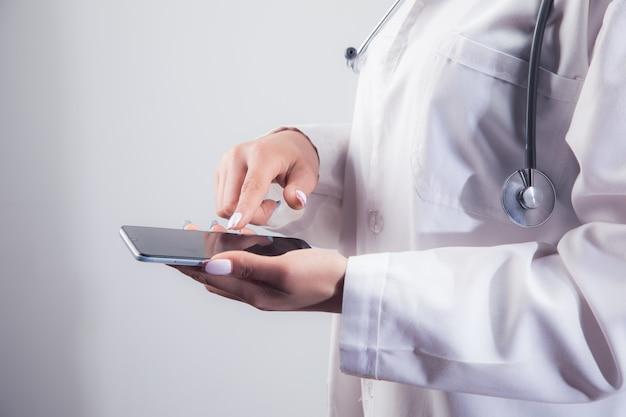 Доктор нажимает на экран телефона