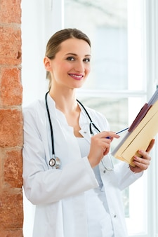 Doctor in clinic writing in a file