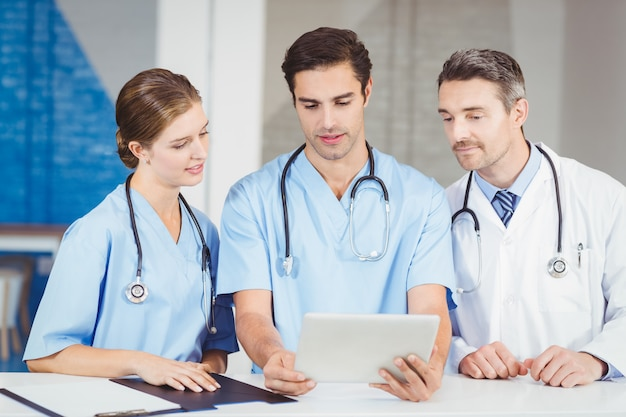 Doctor and colleagues using digital tablet while standing at desk