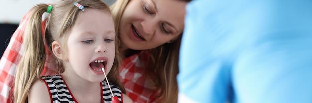 Врач собирает биологический материал из детской слюны